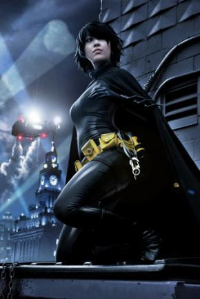 Cassandra Cain, a young Asian-American woman, wears a black cape and looks off into the distance