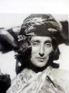 a black and white photograph of hapsa khan wearing a scarf on her head and looking at the camera