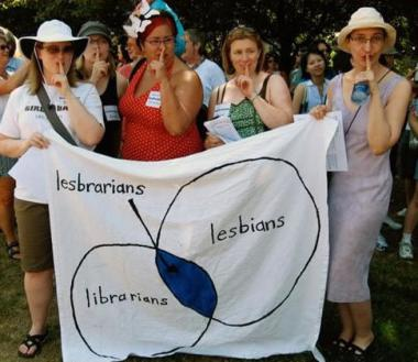 Lesbrarians by Sarah Leavitt: Four women hold a lesbrarians banner at a march, holding their fingers in front of their lips in a shushing gesture