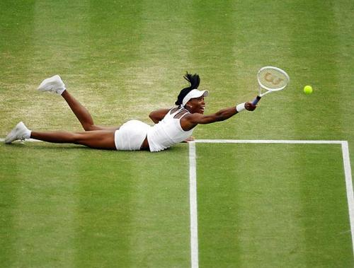 Venus Williams dives on the tennis court to return a shot