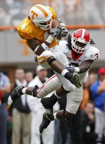 Tennessee's Gerald Jones (4) catches a pass as he's defended by Georgia's Bryan Evans (3) during their college football game on Saturday in Knoxville, Tenn.
